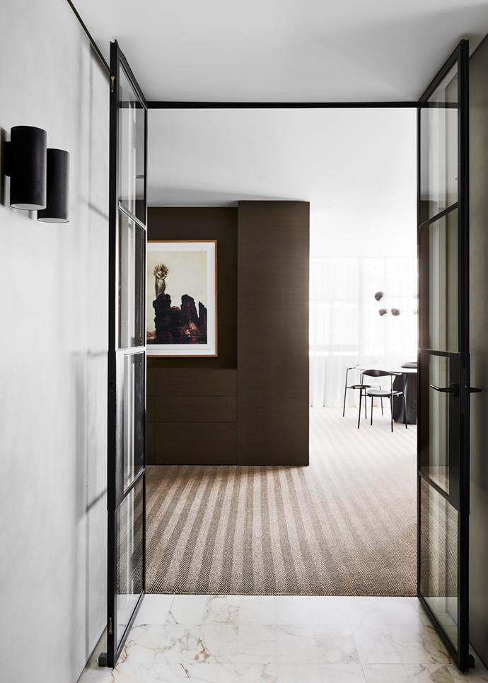 Moving from the entry foyer into the living spaces, steel and glass doors create a sense of arrival while the handsome timber joinery conceals a bar and frames an artwork by Joshua Yeldham from Arthouse Gallery.