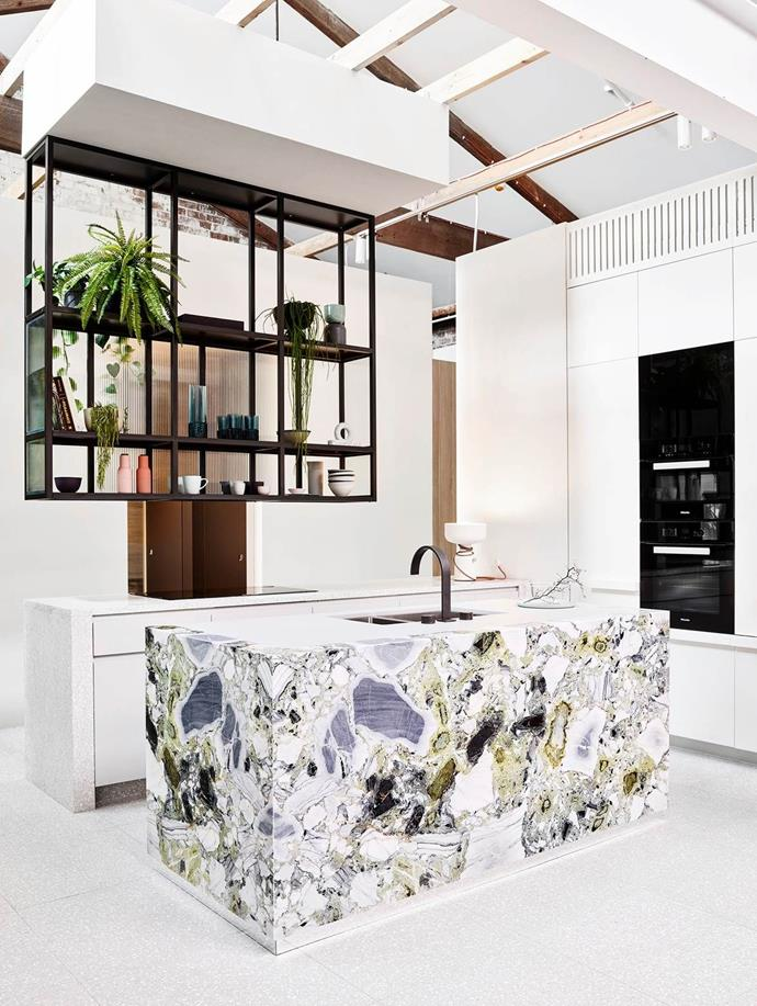 The open-plan layout couples with suspended shelving ensures the stunning stone-covered island remains the focal point of this kitchen. *Photo : Anson Smart*