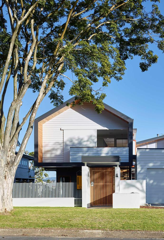 A crisp white weatherboard exterior is paired with rich timber tones in this Scandi-barn style home.