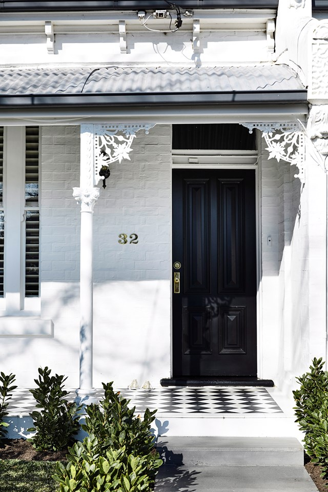 A white painted brick exterior with black accents and statement patterned tiles has refreshed the facade of this Victorian terrace while retaining is heritage charm.