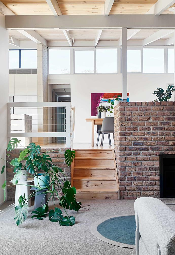 """**Lower living** The original timber stairs and exposed brick fireplace are now features in the new addition. Vitra metal side tables, [Living Edge](https://livingedge.com.au/