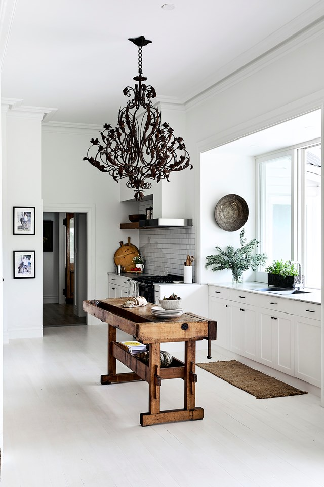 "An antique chandelier hangs above an old European carpenter's bench, adding a rustic touch to the all-white kitchen in this [modern farmhouse](https://www.homestolove.com.au/modern-farmhouse-hills-district-21067|target=""_blank"")."