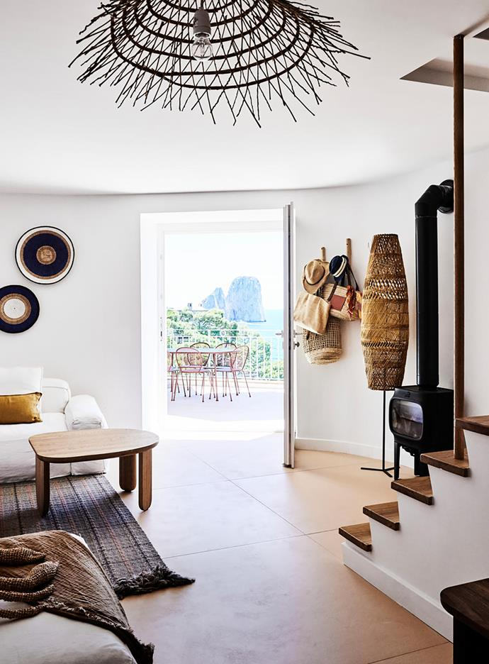 Tactile, handcrafted furnishings warmly embrace the living room's pared-back architectural details. The white sofas and round African wall baskets are from The Conran Shop and the handwoven ceiling pendant and floor lamp are from Mona Market. The Jøtul cast-iron stove provides respite from the cold winters.