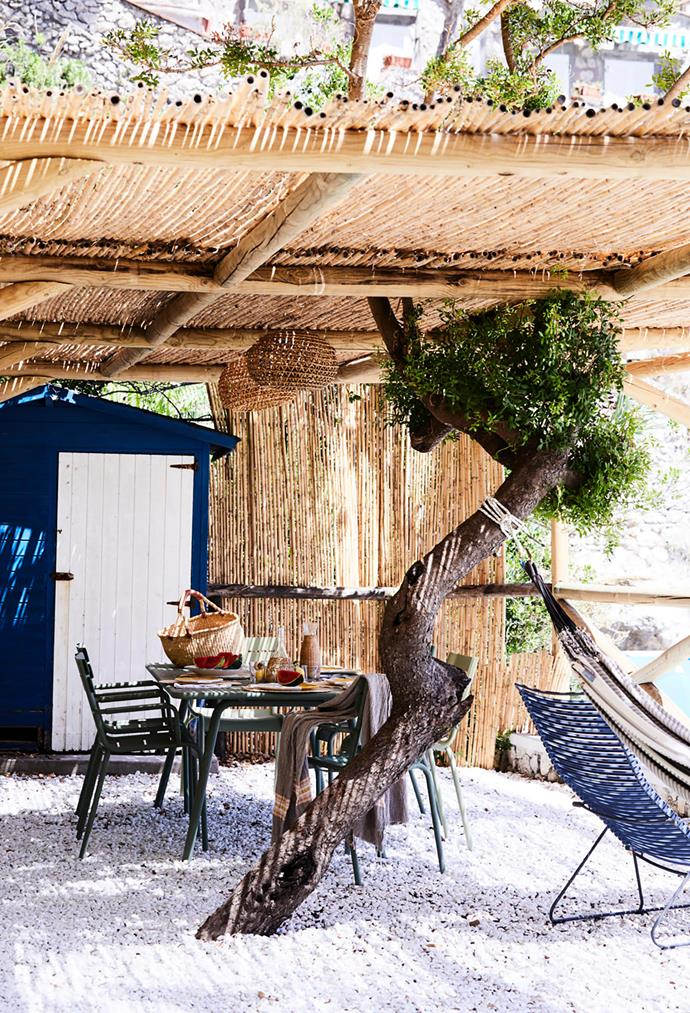 A bamboo pergola with a dining table and chairs from Fermob and a hammock brought back from Florence maximise the property's close proximity to the water. This sandy spot is ideal for picnics and the little blue cabin is used to store the family's beach gear.