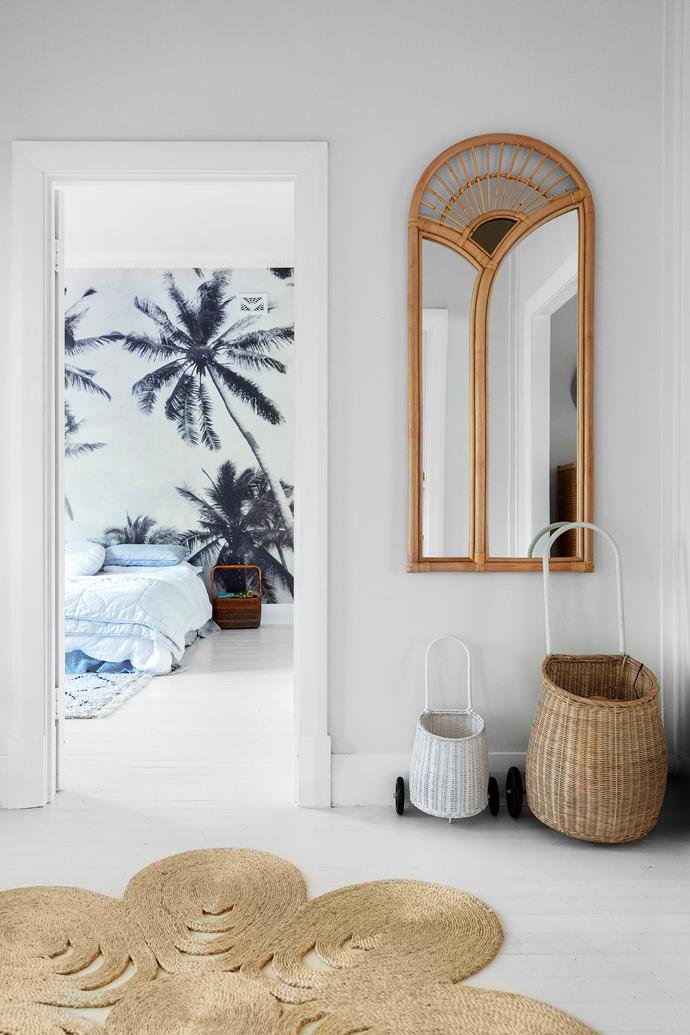 Natural materials are woven throughout the home, starting with this cane mirror and petal-shaped rug from Etsy in the entry. Dee and Rafa wheel these straw Olli Ella 'Luggy' trolley baskets around the local weekend markets.