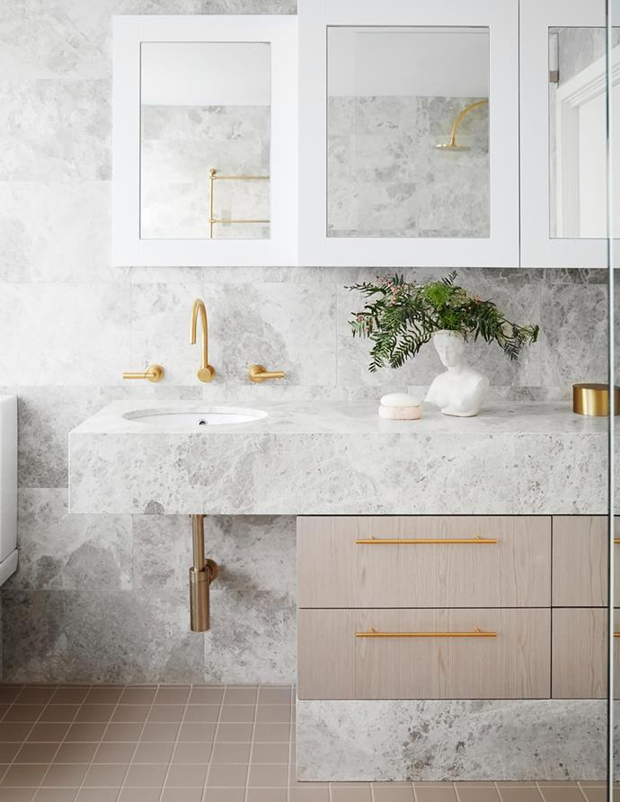Vanity fronts in Ayous engineered-timber veneer in Alabaster, Slice Veneers. Brass drawer pulls, Style Finish Design. Silver Casa honed-limestone wall tiles, SNB Stone. Vogue ceramic floor tiles in Tortora, Classic Ceramics. Aphrodite Deux Fois bust, Degoey Planet.