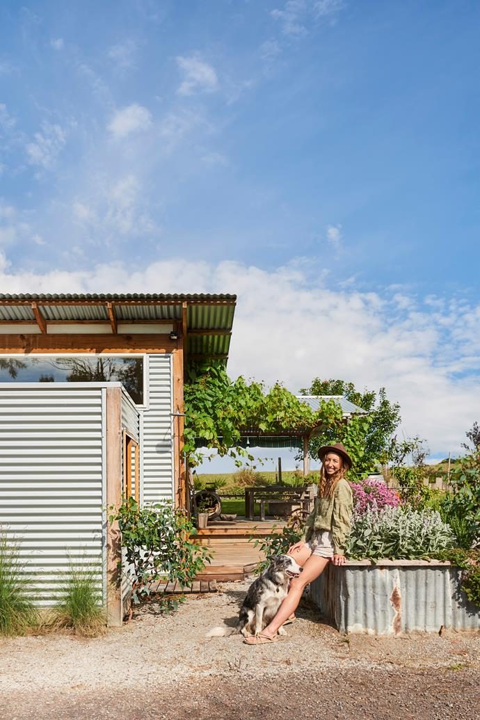 Harriet Birrell and her koolie border collie cross Fred out the front of her corrugated iron-clad home.