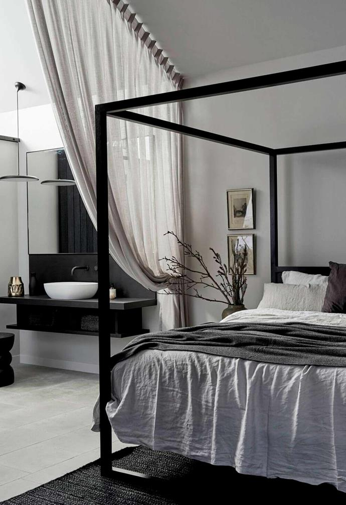 "A statement [bed frame](https://www.homestolove.com.au/bed-frame-7010|target=""_blank"") can anchor your bedroom just like this dramatic black canopy bed at The Bower. Multi-layered linen bedding and pillows add depth and visual interest within the bedroom."