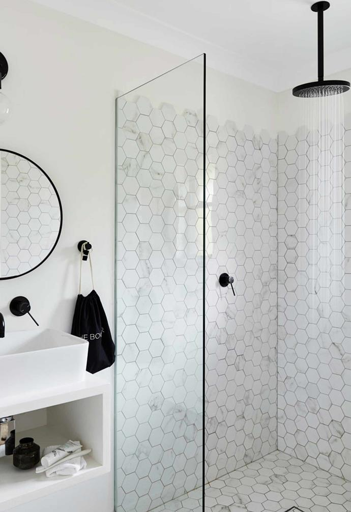 Playing with monochrome doesn't mean you have to have a boring bathroom, either. The marble hexagon tiles that line the shower in this bathroom add a striking visual look.