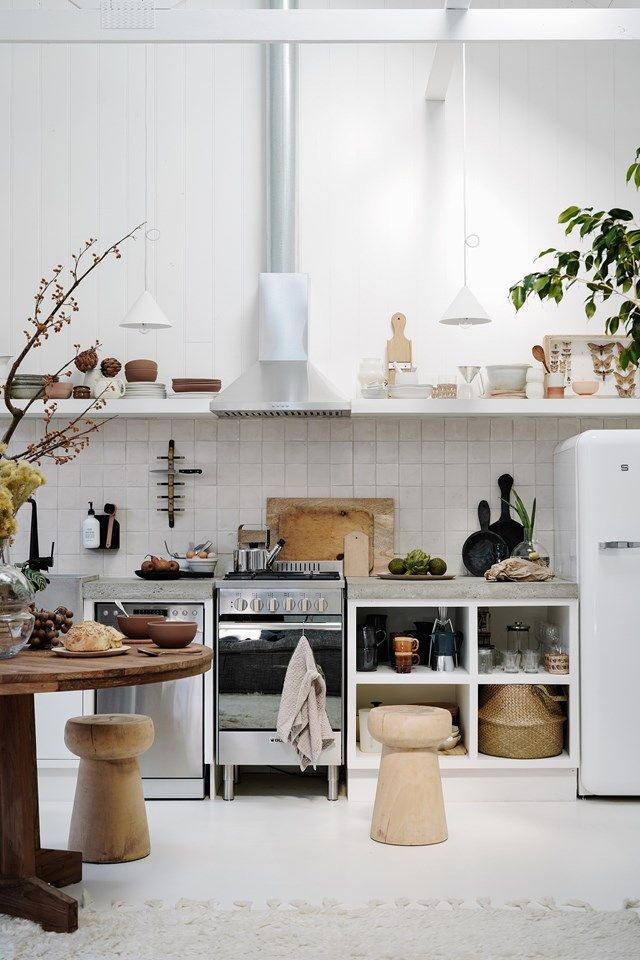 "In this open-plan studio, the kitchen has been designed to connect seamlessly with the rest of the space. The key to creating a cohesive look within an open-plan space is a considered colour scheme and here, a simple palette of white, concrete and timber gives the [barn-style home](https://www.homestolove.com.au/small-barn-style-home-21098|target=""_blank"") an industrial feel."