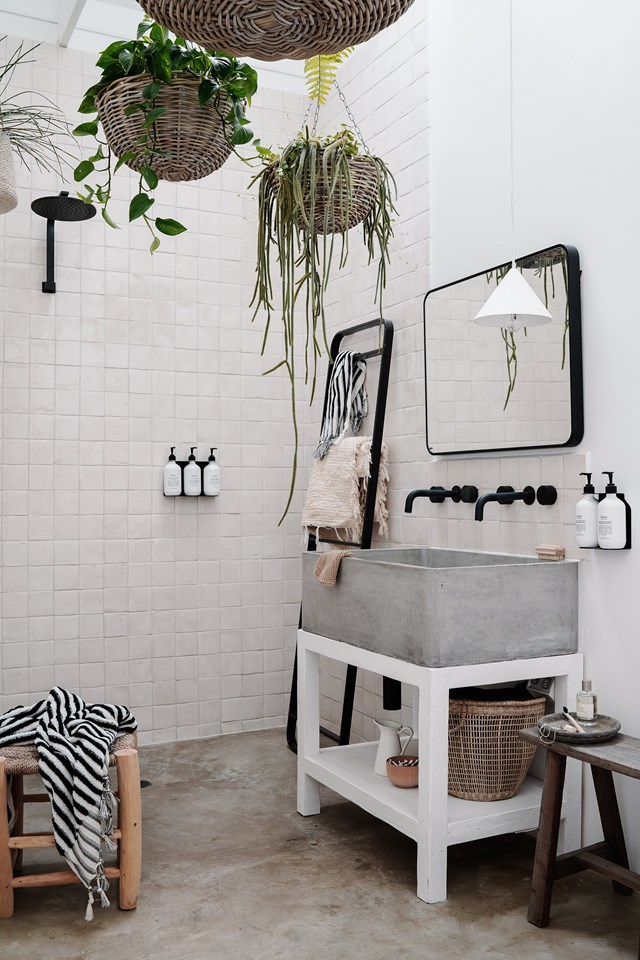 Handmade tiles and concrete surfaces give this modern bathroom a raw and rustic feel, while timber furniture and woven baskets add warmth and decorative flair.