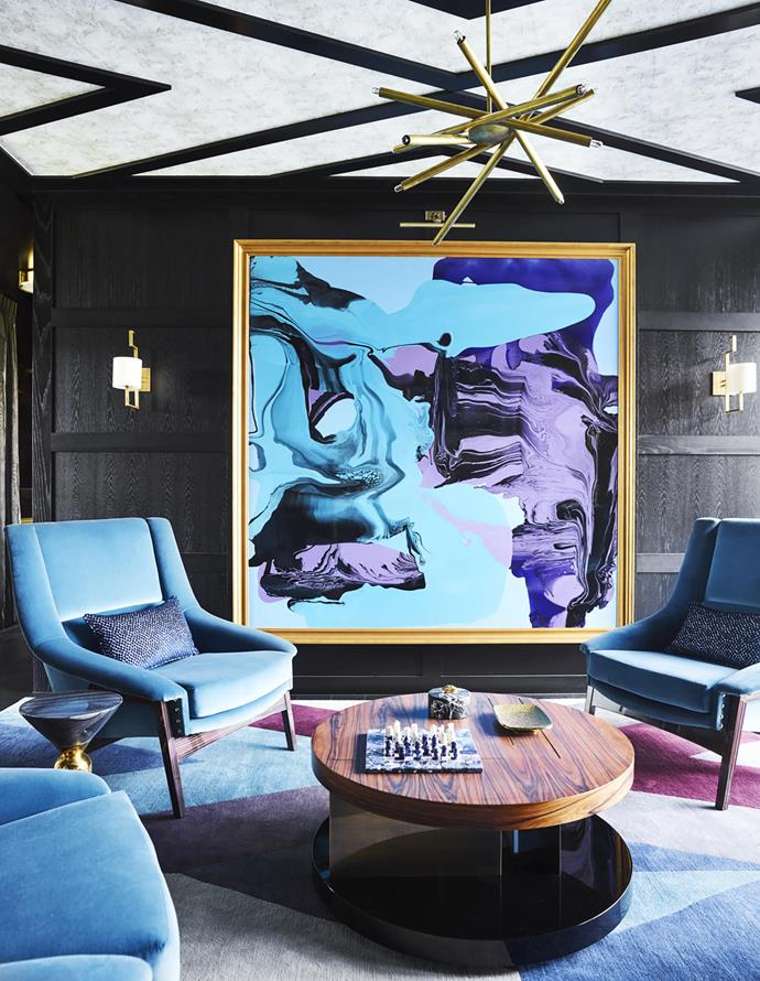 Mick Jagger artwork by Andy Warhol. In the reading nook, 'Inca' armchairs and 'Lallan Center' coffee table from Brabbu. 'Spiral VL-6' brass chandelier from Gallery L7, LA. Artwork by Dale Frank.