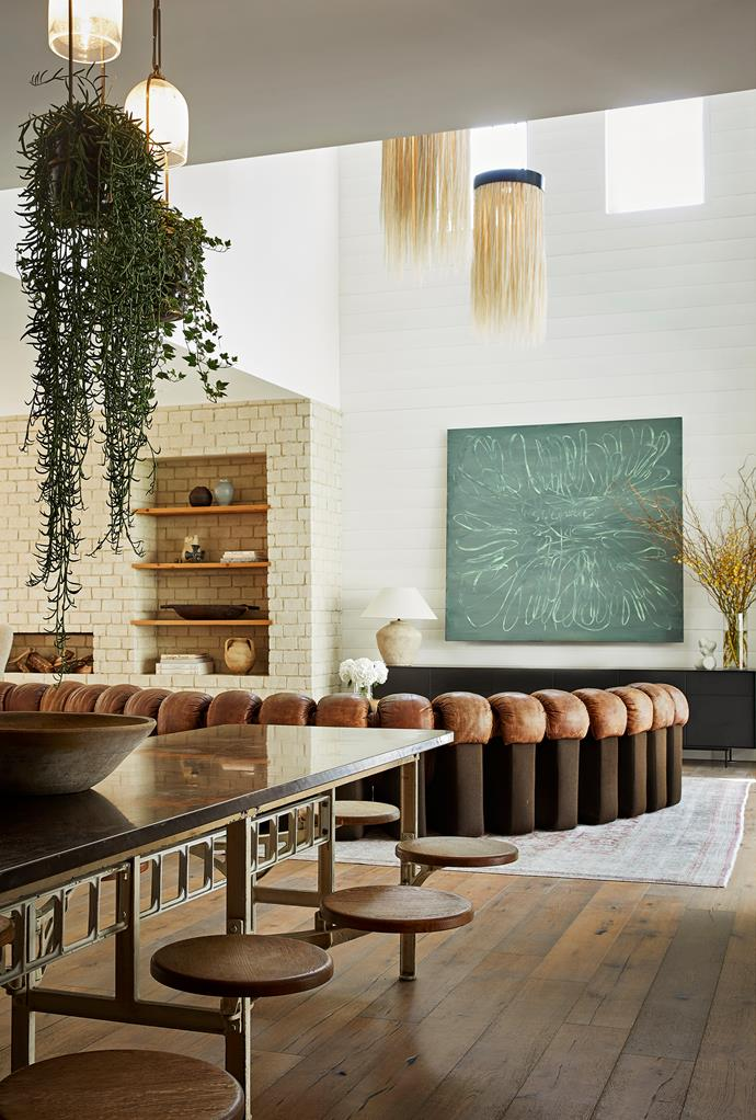 The horizontal shiplap walls and hand-painted brick fireplace were designed to create a warm, informal mood in the open living area. A de Sede sofa and Formica worktop table with swing chairs facilitate casual seating arrangements, while the Peter Bonde artwork cleverly conceals a television behind it. Siglo Moderno 'Growlights' form a leafy canopy above.