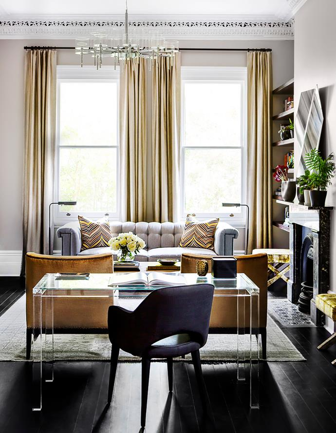 A Lucite desk with a custom glass top by Brendan Wong is positioned to give a view over the formal sitting area. Vintage chair from LA.