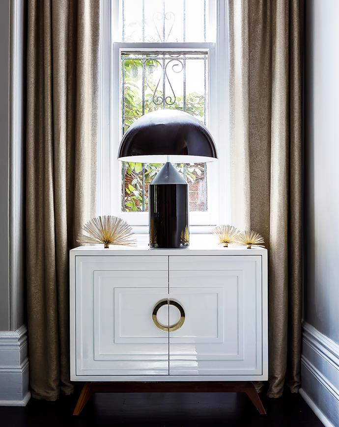 Oluce 'Atollo' lamp sits on a lacquer and brass credenza.