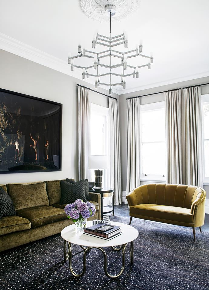 In the informal sitting area is a sofa upholstered in Schumacher 'Gainsborough' velvet. Jonathan Adler coffee table. Rug by Robyn Cosgrove. Nemo 'Crown Major' lightfitting. Photograph is By Feel by Tamara Dean.