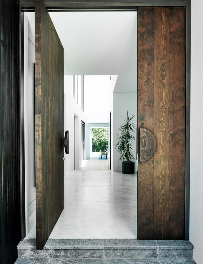 """I love the front door and the view through the hall to the back lawn,"" says Polly. ""It reminds me of a Californian desert house."" The western red cedar pivot door has a 30cm black-stained timber-disc handle."