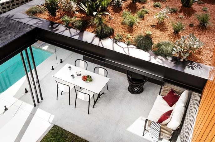 All the landscaping was a joint project between Dalecki Design and Limitless Building. The flooring is concrete. Vitra outdoor dining table and chairs, Living Edge. Driade black lounger and outdoor sofa, Ultimo Interiors. Teapot, Marimekko. Cups and platter, Mud Australia.