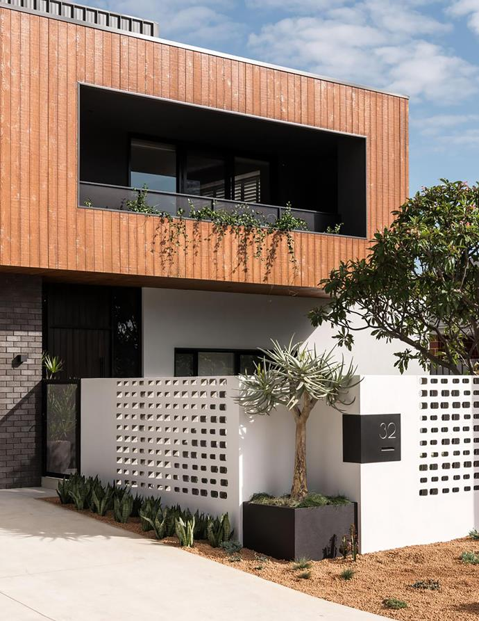 Sam and Sarah requested a contemporary 'box on box' front elevation. The upper-level cladding is Weathertex Weathergroove. An aloe tree grows in the wall niche, while Chinese star jasmine spills softly from the balcony. For Where to Buy, see page 222.  #