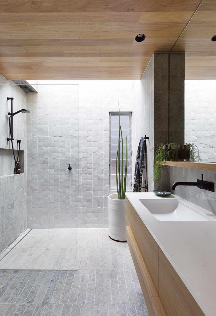 """**Subtle touch** Pale grey shades are celebrated in this bathroom through raw texture and interesting variations in form. Handmade Moroccan tiles line the shower walls and floor while rectangular limestone tiles feature on the bathroom floor. Light-toned timber brings a designer edge to the room with the vanity crafted by All Aspects Joinery in [Laminex](https://www.laminex.com.au/
