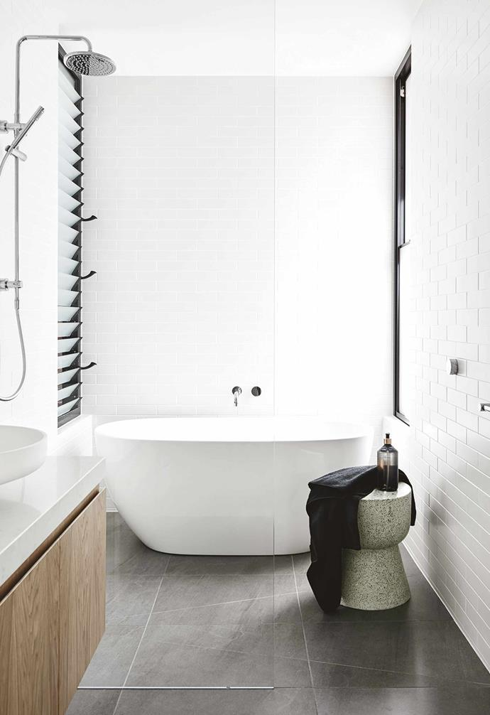 """**Side to side** A slender passage of natural light is all you need to make a bathroom feel that little bit bigger. This space has the bonus of two, with a set of louvre windows matching the lines of the wall tiles from Lifestiles. The Kado 'Lux Petite' bath from [Reece](https://www.reece.com.au/