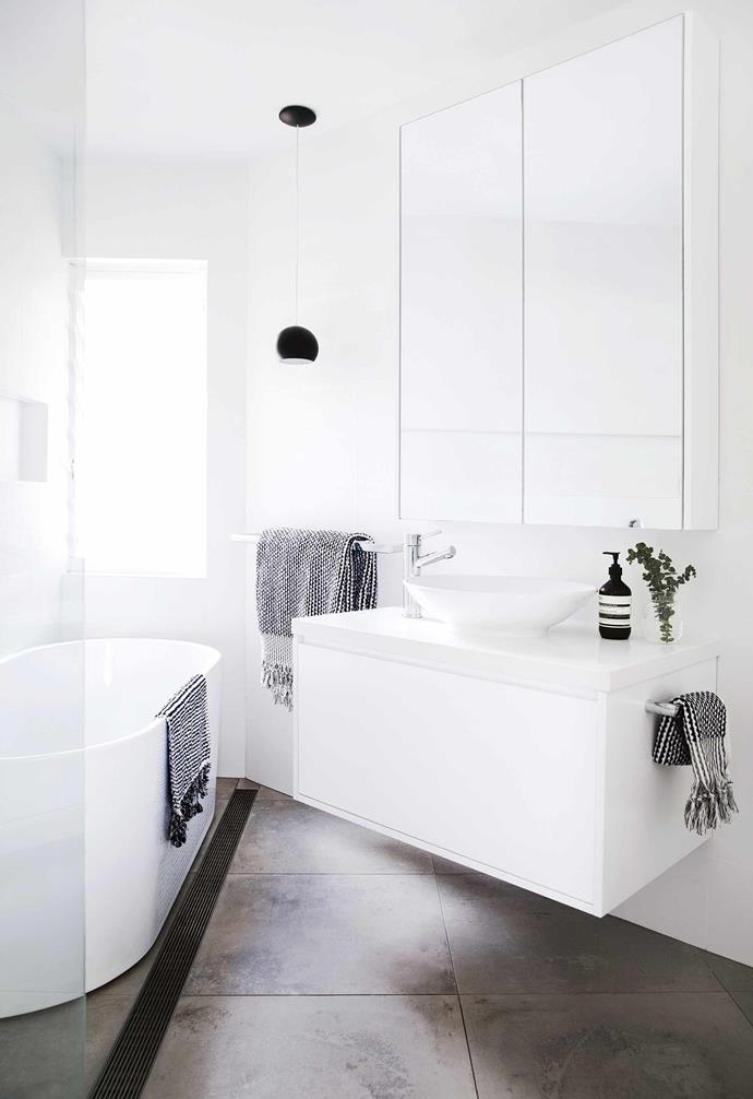 """**Clean and serene** This small space packs a lot of bathroom: a mirrored wall cabinet, wall-hung vanity, a shower and a bath. The bathroom in [this minimalist apartment](https://www.homestolove.com.au/minimalist-apartment-northern-beaches-17911