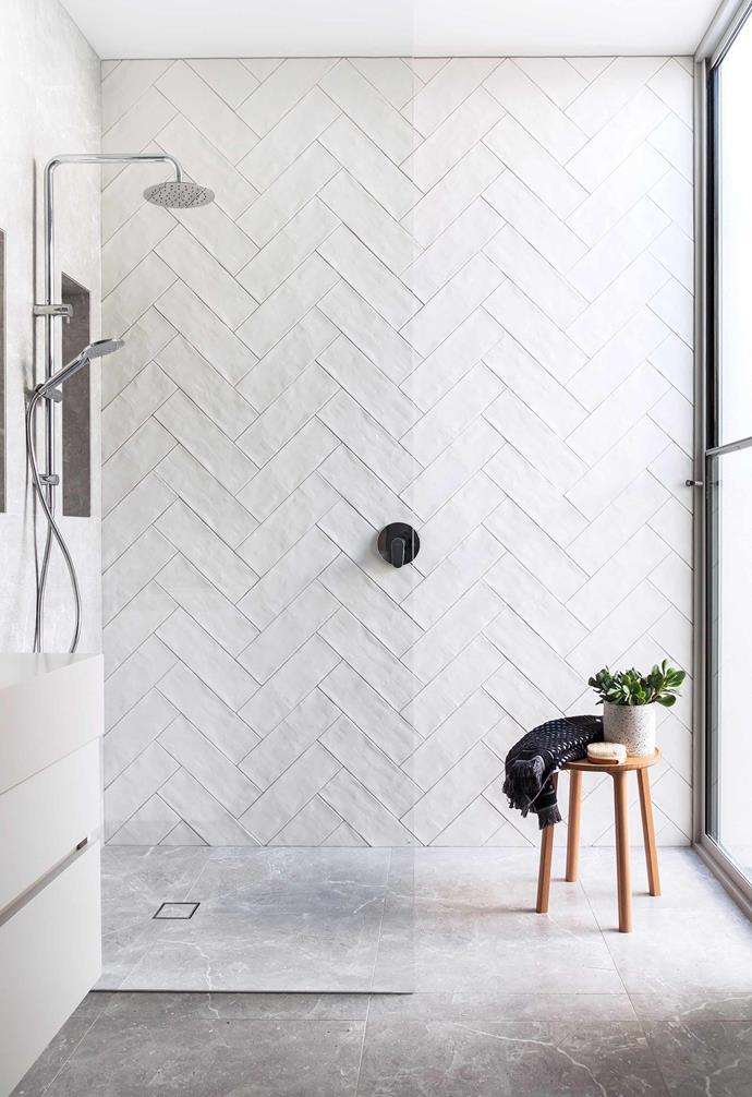 **Tactile style** The owners of this Victorian home in Williamstown felt the house was suffering from a bad 1990s hangover. Period features were restored to the facade, but the bathrooms had a contemporary overlay, using neutral tones with Ocean Grey Honed tiles from Elegance Tiles on floors and walls, and a feature wall of the Self 'Mood' white matte tiles laid in a herringbone pattern. The shower is a Phoenix 'Vivid Slimline' twin shower.<br><br>