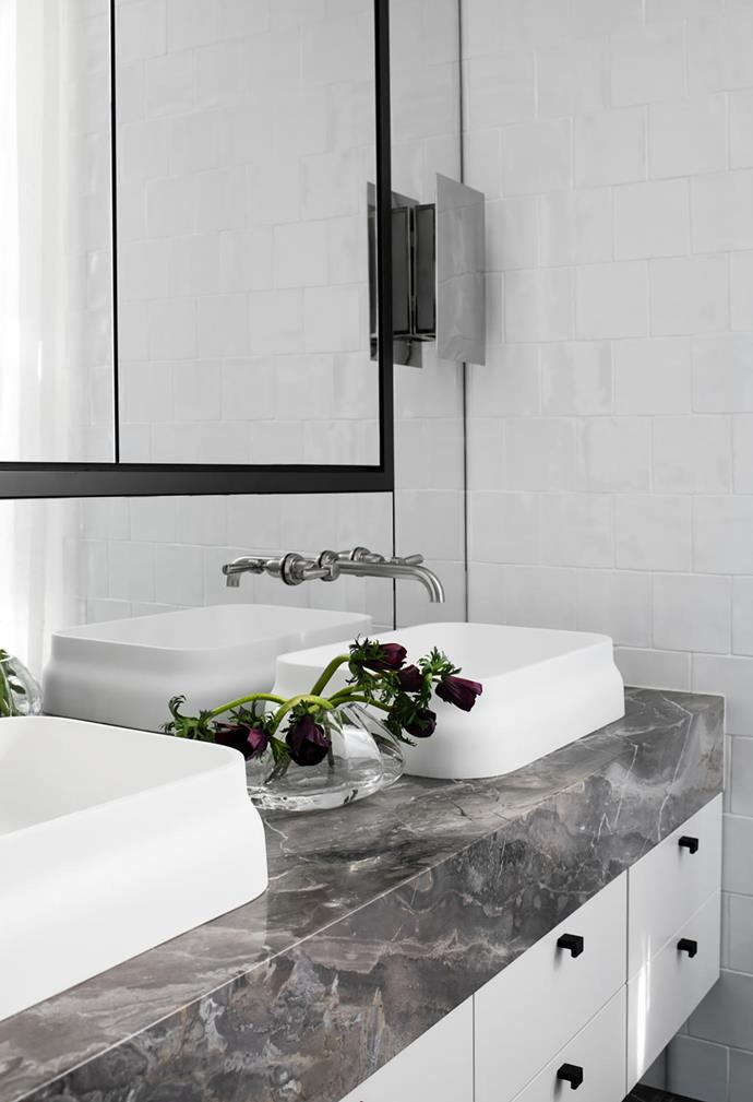 In the ensuite, a luxurious slab of Arabescato Orobico marble clads the vanity. Basins from Candana with tapware from Brodware. Wall sconces by Porta Romana.