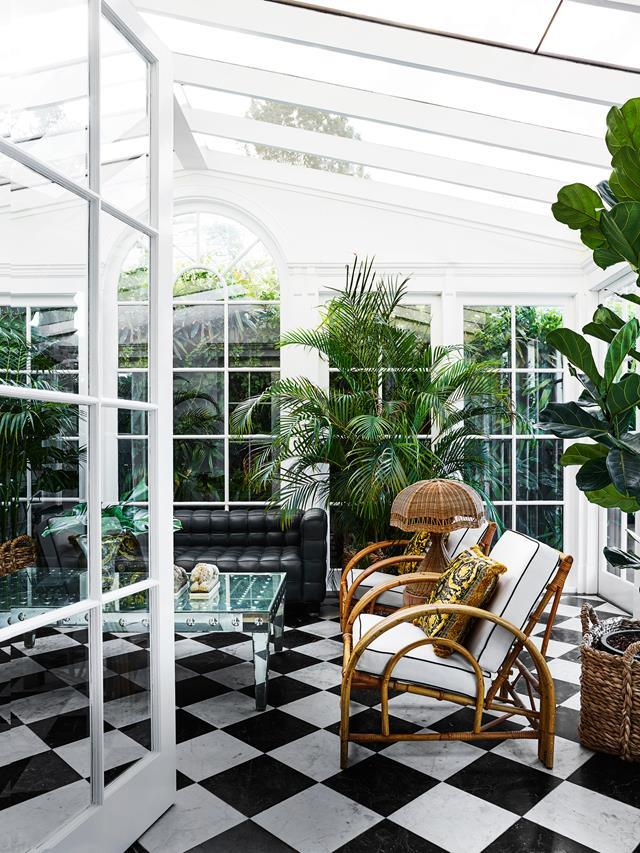 "On ground level at the rear of this [heritage home](https://www.homestolove.com.au/youthful-redesign-of-a-historic-heritage-home-6113|target=""_blank""), a sunroom has been transformed into a Bahamas-plantation-style glasshouse drenched in light. Tamsin Johnson confessed to going ""a bit crazy with the palms and planting,"" but the soaring ceiling and double doors opening onto the lush garden was the perfect setting. ""The process was the bigger the better, I really wanted to bring the outdoors in."""