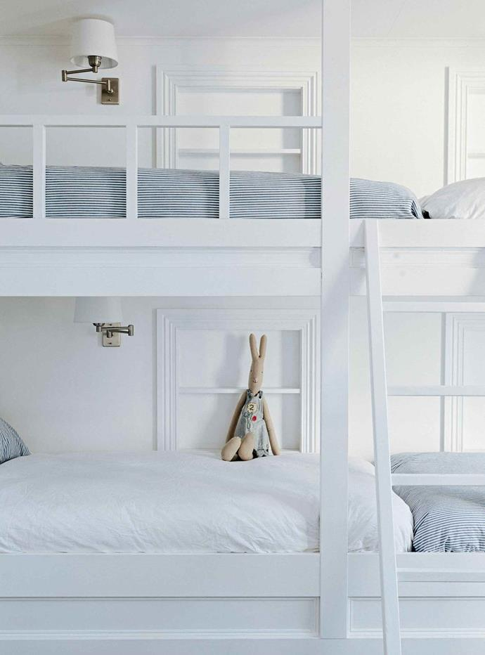 Bunk beds are great space savers and a calming all-white colour scheme will make a small room feel spacious and calming. Here, linen in blue ticking fabric add subdued colour while extendable wall lamps add another layer of functionality.