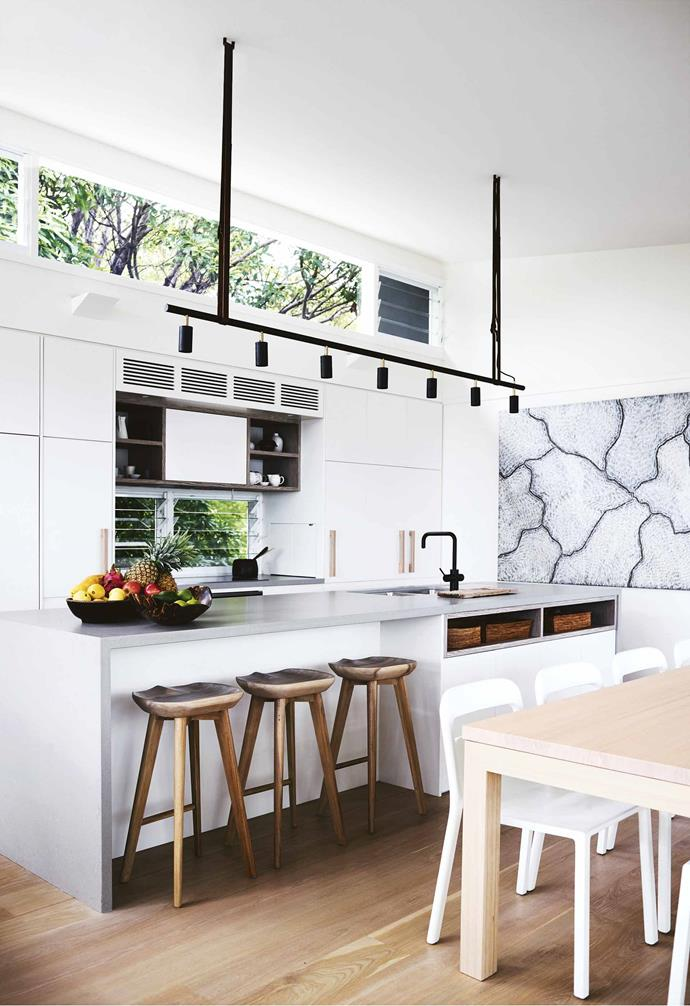 """Contrary to the myth that Byron's full of surfing layabouts, there are a lot of talented people who are here for the lifestyle,"" says Philip.<br><br>**Kitchen** A Sarrita King artwork sets a refined tone. The Caesarstone benchtop in Raw Concrete is a hardy surface in this busy zone, while the Zip HydroTap eliminates the need for bought sparkling water. The Rubn Lighting 'Long John' pendant light from [Fred International](https://fredinternational.com.au/
