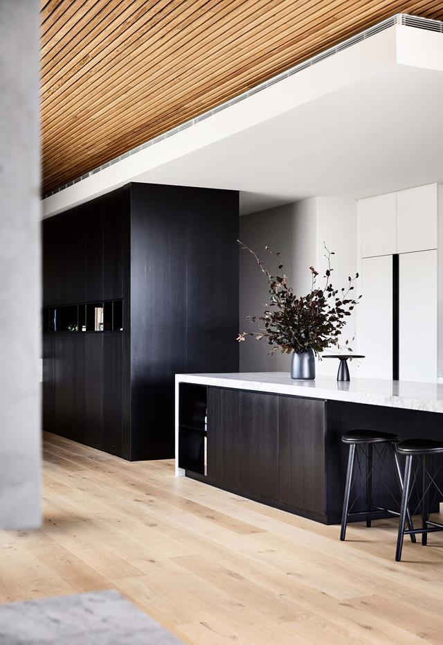 "[This penthouse](https://www.homestolove.com.au/a-sophisticated-entertainers-penthouse-in-brighton-18857|target=""_blank"") was a four-year project by Vanda and Tom Robertson Architects that began with the purchase of an old office building. Bec van der Sluys called on Simone Haag to collaborate with her on styling the interiors. Black kitchen cabinetry adds warmth to the interior scheme under the timber ceiling that runs along the central corridor."