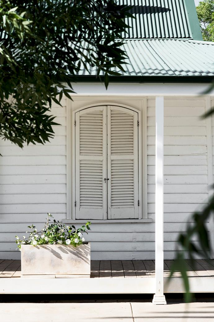 The house was built in the 1880s. Timber shutters cover original arched windows.