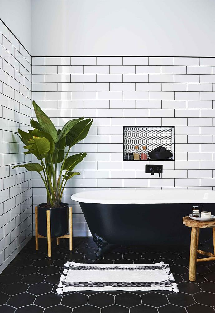 "The geometric pattern formed by black hexagon tiles with white grout on the floor contrast dramatically with the white subway tiles on the wall, and are tied together with a black and white clawfoot bath tub in the bathroom of this [country farmhouse](https://www.homestolove.com.au/country-farmhouse-17468|target=""_blank"")."