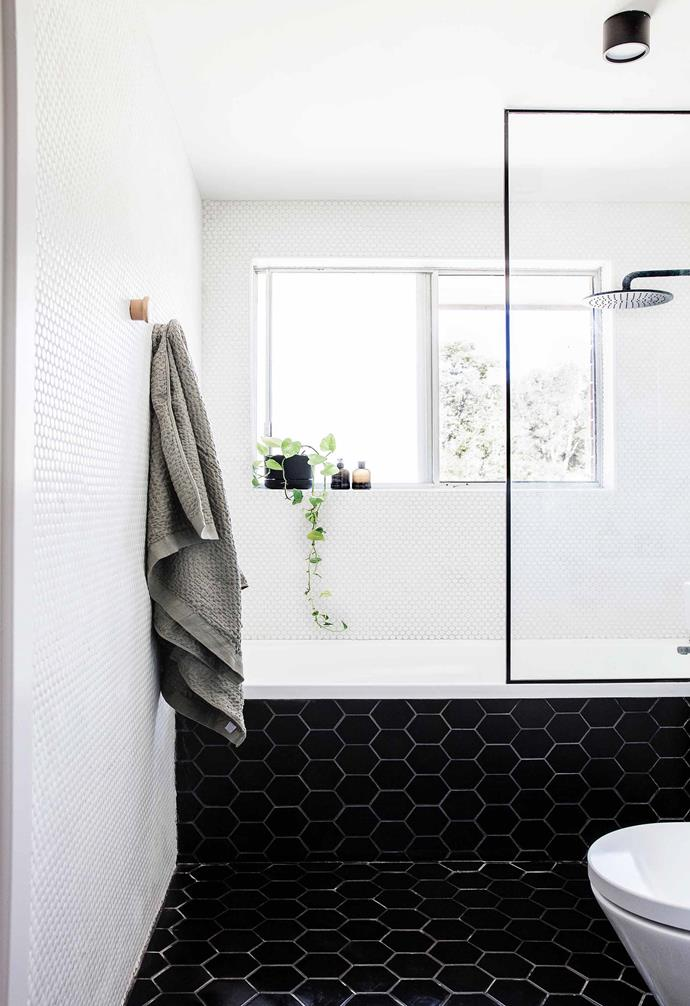 "Matte hexagonal black floor tiles are paired with white pennyround tiles on the wall for a playful look in the bathroom of this [renovated coastal apartment](https://www.homestolove.com.au/coastal-apartment-renovation-19053|target=""_blank"")."