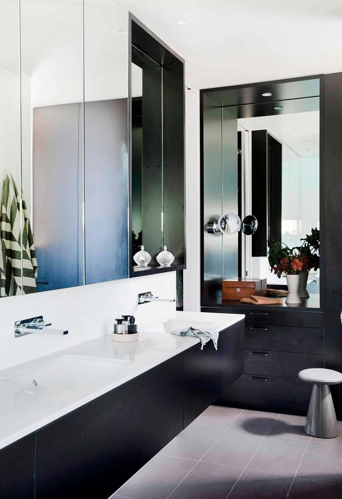 "Black cabinetry and generous mirrors abound in the bathroom of this [home in Riverview](https://www.homestolove.com.au/nature-inspired-house-riverview-20198|target=""_blank""), but a slim-line benchtop with inset basins add a bright contrast."