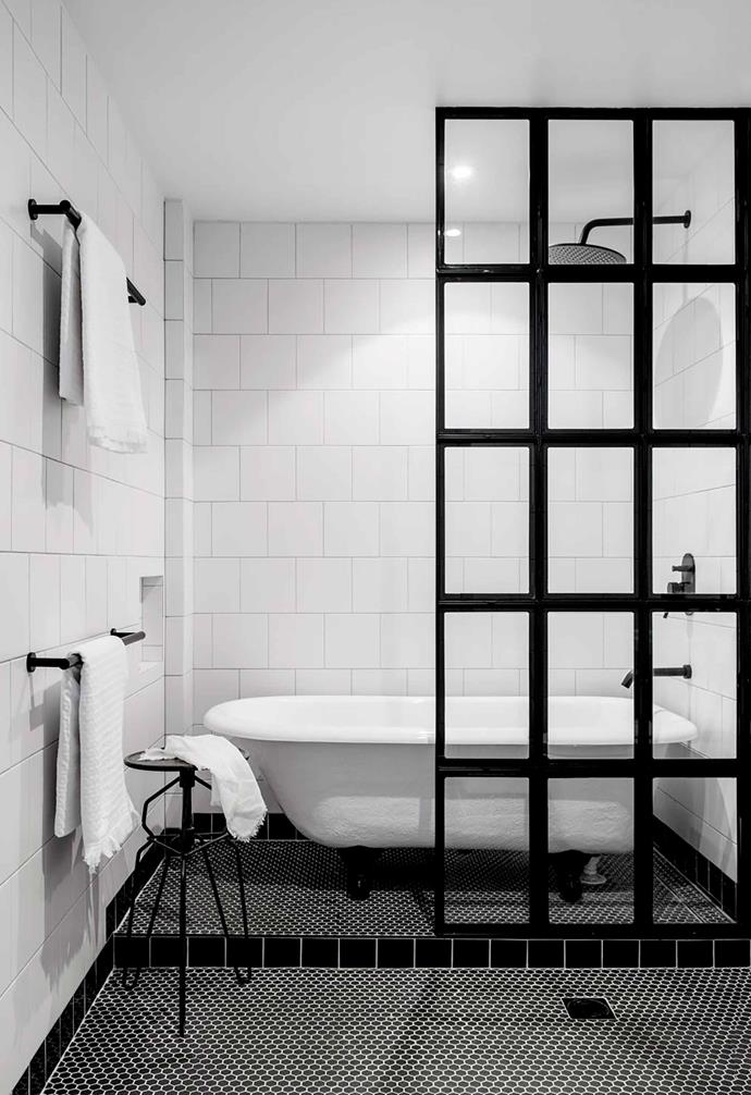 A stylish black statement screen pops against white square tiles on the walls in the bathroom of this industrial-style apartment. Black pennyround tiles with white grout add a striking feature.