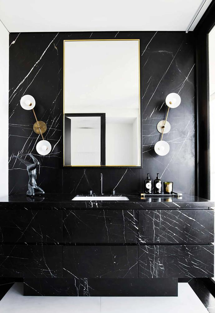"In this glamourous [Sydney apartment](https://www.homestolove.com.au/a-luxe-sydney-apartment-with-bespoke-interiors-19676|target=""_blank"") a statement black marble custom vanity is the hero feature in the bathroom. With the entire wall clad in black marble with white veins, the surrounding walls and ceiling provide a dramatic contrast in white."