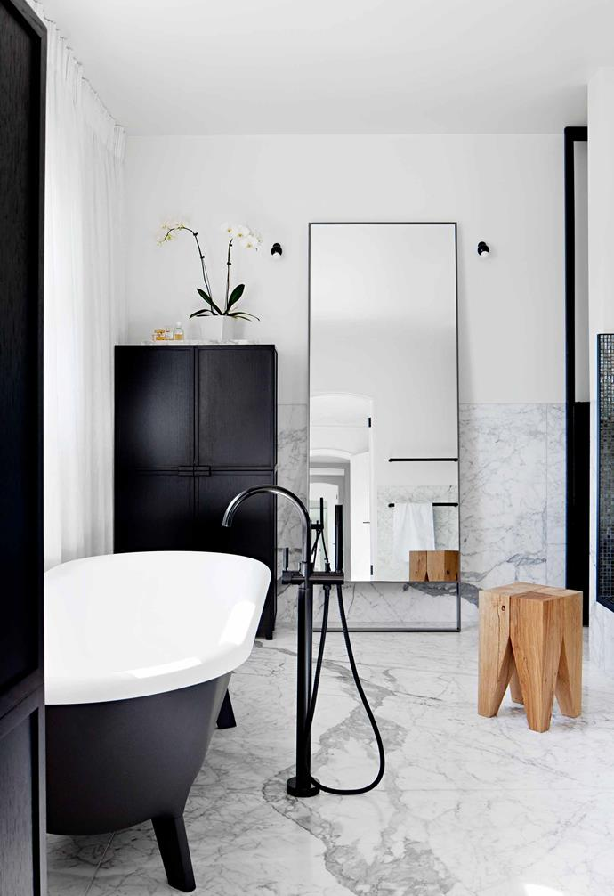 "The black and white colour palette in the bathroom in this [Melbourne home](https://www.homestolove.com.au/family-home-reinvented-with-classic-contemporary-style-6793|target=""_blank"") makes the most of its natural light, with the black cabinetry and bathtub exterior adding depth to the space."