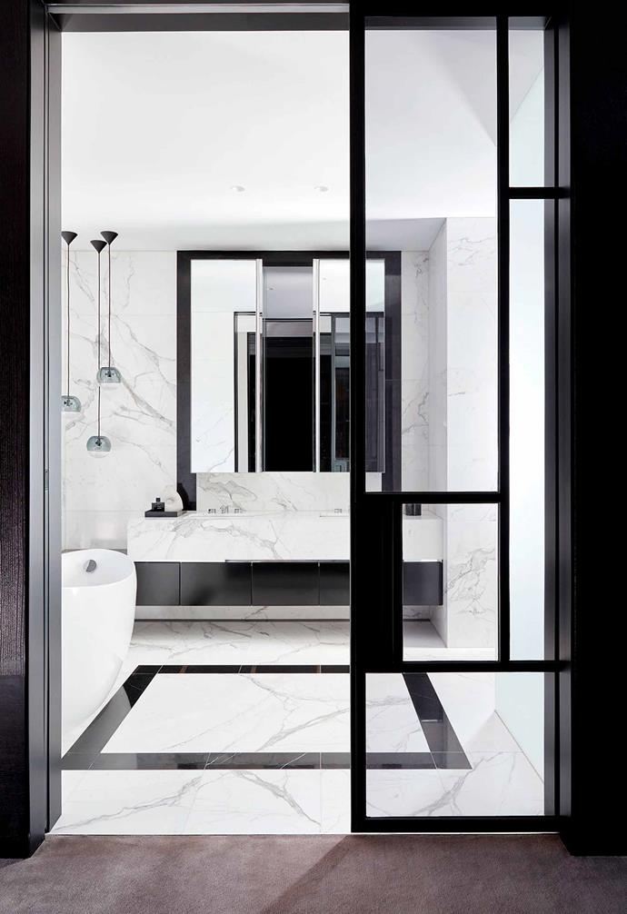 "Black steel-framed doors welcome you into the bathroom in this [monochromatic Toorak home](https://www.homestolove.com.au/monochromatic-home-melbourne-toorak-6270|target=""_blank"") where white marble is paired with black accents for a luxurious touch."