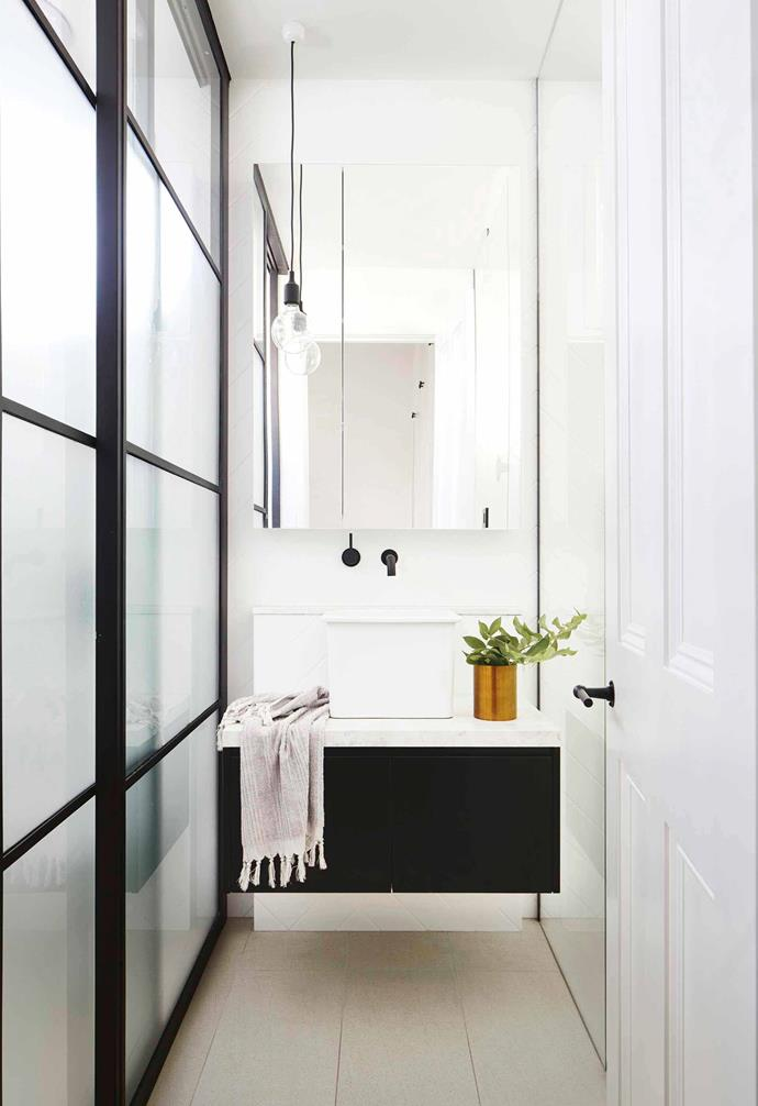 "The black vanity unit in the bathroom of this [Scandi-style home](https://www.homestolove.com.au/scandi-style-glass-house-extension-17515|target=""_blank"") grounds the sun-soaked room."