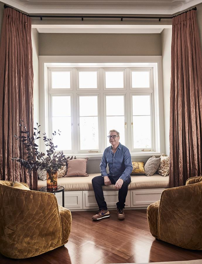 Interior designer Brett Mickan tests out the window seat. Curtains in Mokum Couture fabric from James Dunlop Textiles.