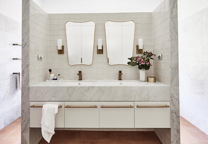 Clever features abound in the couple's ensuite. Vanity topped with Carrara marble from Granite & Marble Works. Drawer pulls, Savage Design. Gubi mirrors, Cult. Evergreen wall sconces, Robert Long Lighting. Elk basin mixers, and Icon heated towel rails, Astra Walker.