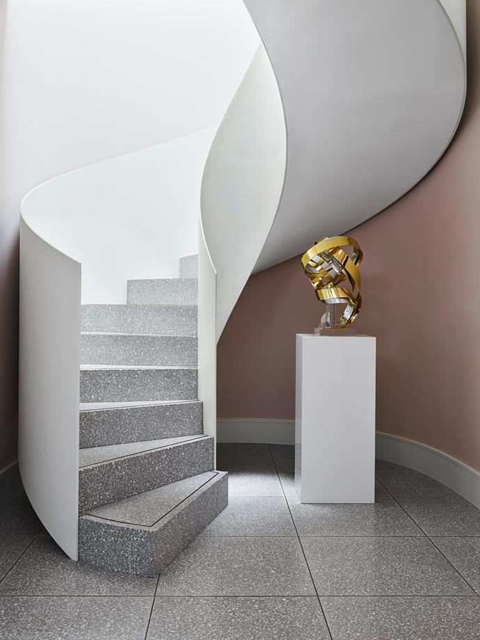 The curve is also celebrated in the glorious spiral staircase. Sculpture by Dan Murphy from the Greg Natale flagship store. Terrazzo stone flooring with brass inlays from Terrazzo Australian Marble. Staircase by Ciolino Constructions. Walls in half-strength low-sheen Dulux 'Portrait Pink'.
