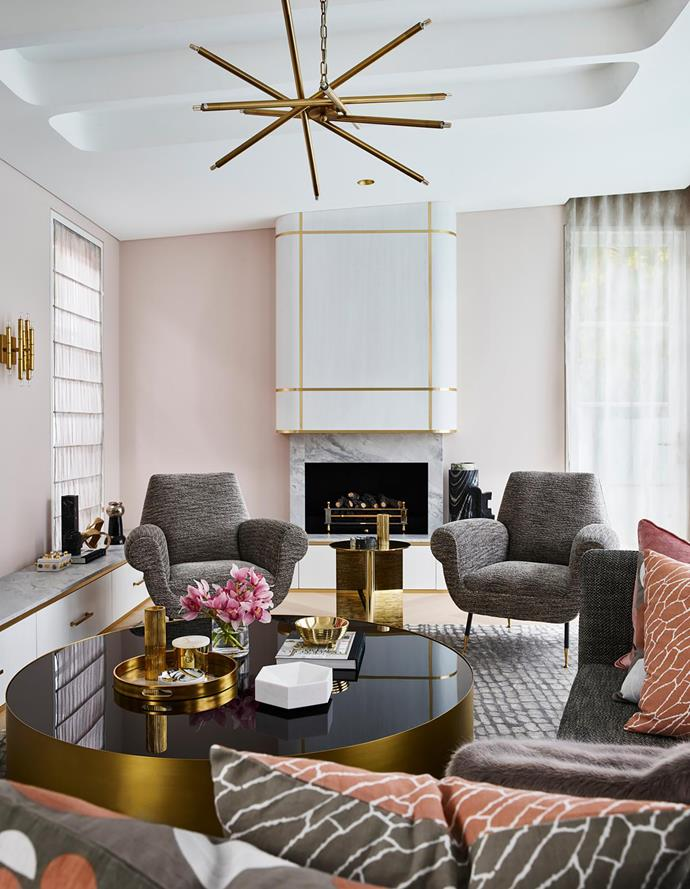 Brass accents lend a sense of luxe to the living area. 'Luisa' brass chandelier from James Said. Vintage Minotti 'Albert & Ile' armchairs from Stephen Conley of Conley & Co. 'Moore' coffee table from RH. Atelier De Troupe 'OS' side table from Spence & Lyda. Greg Natale 'Hide' rug from Designer Rugs. Cushions and brass and marble accessories, all from Greg Natale.
