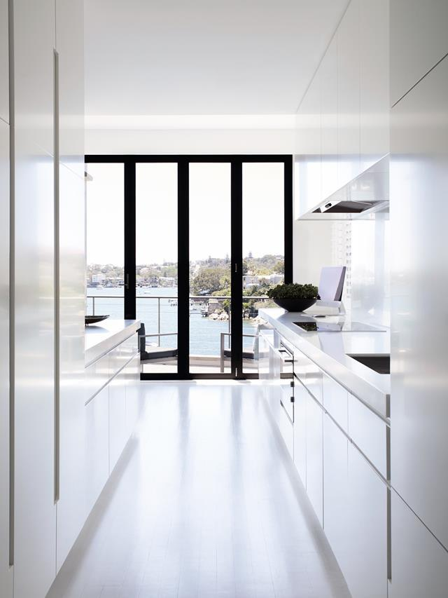 "Creating a connection with the view was one of the major objectives for interior designer Brooke Aitken in the renovation of this [luxurious harbourside home](https://www.homestolove.com.au/a-luxurious-resort-style-home-overlooking-sydneys-parsley-bay-6526|target=""_blank""). The kitchen is white and minimal, a foil for the decorative ceiling of the dining/living room to which it is connected."