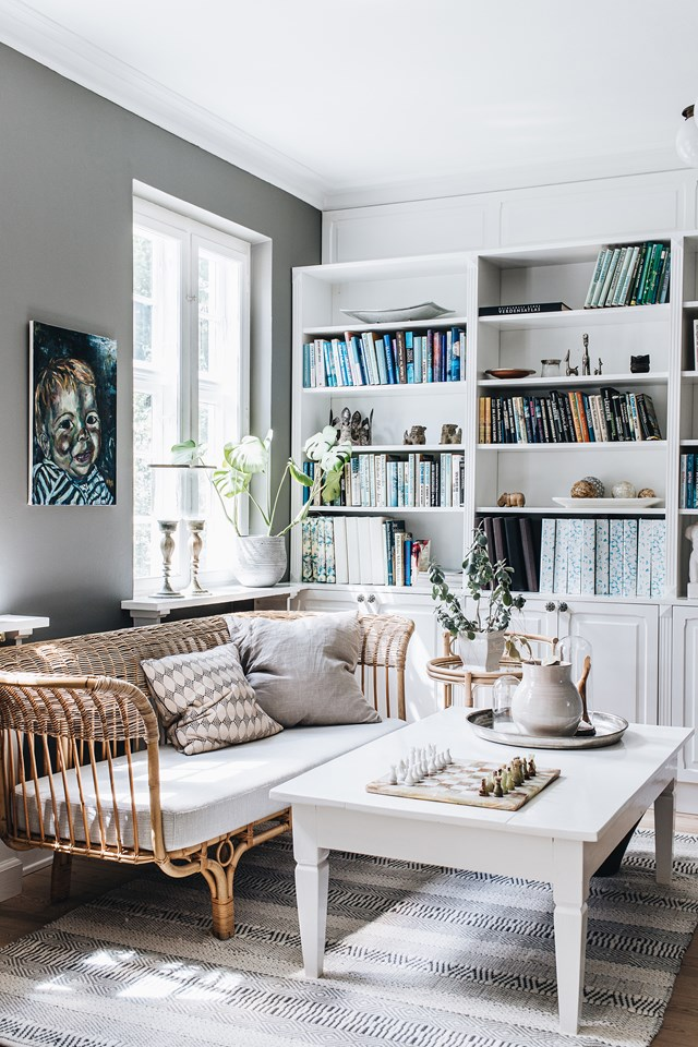 "The living room in this [dreamy Denmark home](https://www.homestolove.com.au/danish-interior-design-21159|target=""_blank"") has been designed with downtime in mind. A built-in bookshelf, filled with treasured tomes, occupies an entire wall and a chess board is always on the go. Dappled light and indoor plants only add to the ambience."