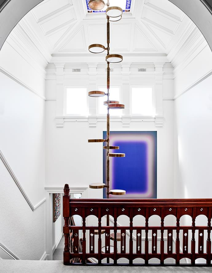 A dramatic 8.5-metre brass pendant light from Ms Arredamenti in Italy drops down into the light-filled stairwell where Promise to Come Back artwork by Jonny Niesche is framed in mirrors.