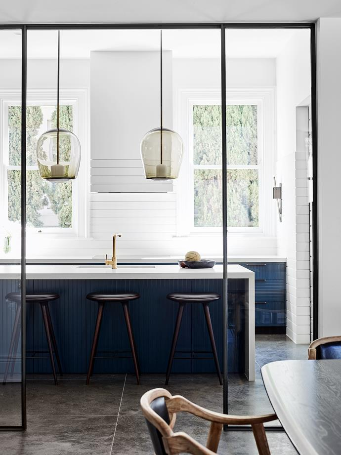 Clean lines characterise the kitchen, where steel and glass blade walls have been inserted to delineate the area. Stools sourced at Leonard Joel and 'Molten' pendant lights from Holly Hunt.