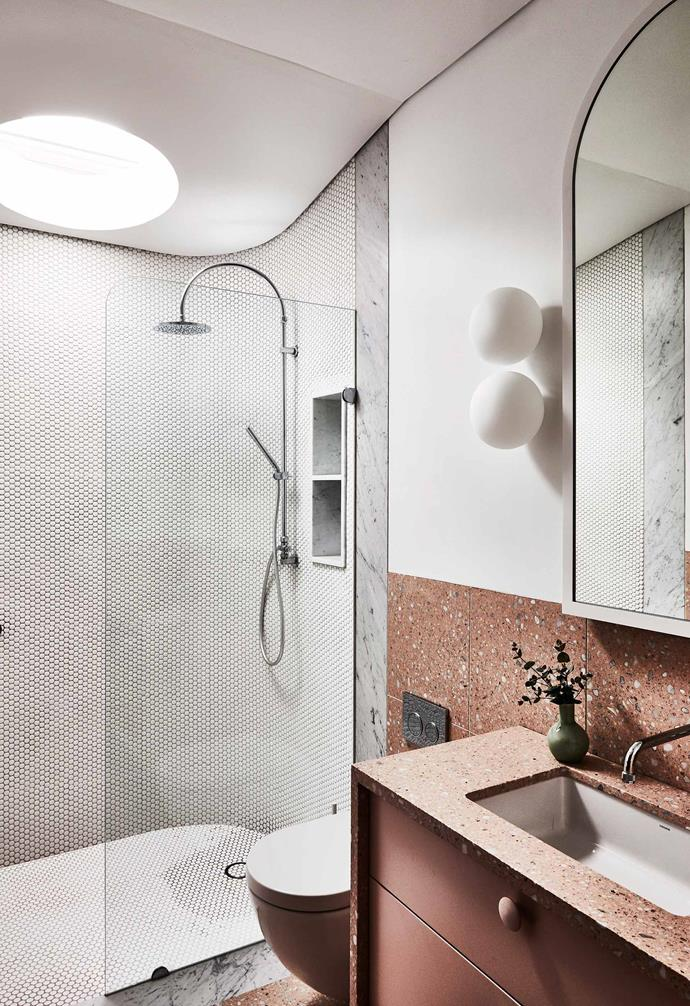 Terracotta-toned terrazzo tiles sing in this chic bathroom space where a circular skylight floods the walk-in shower with natural light.